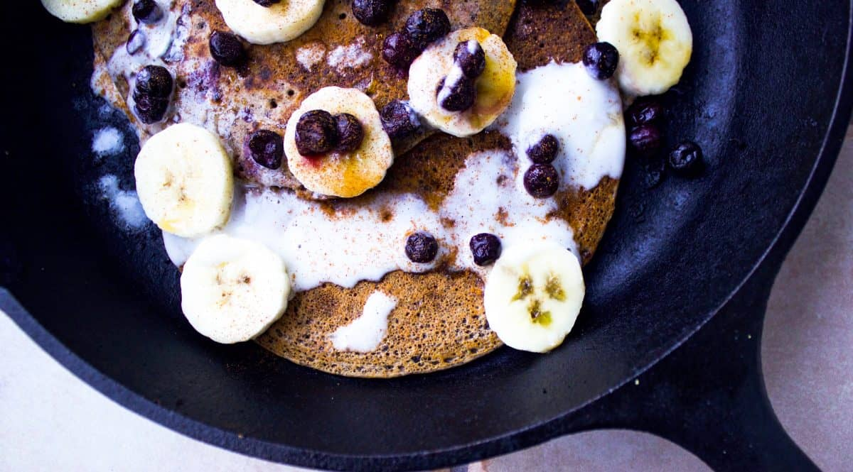 Overhead image of buckwheat maple pancakes in cast iron skillet, showing pancakes with banana slices, blueberries and coconut cream drizzled over.