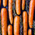 Vegan Christmas Recipes. Roasted Maple Rosemary Carrots (vegan + gf). Overhead image shows roasted carrots on a black baking sheet with sprigs of rosemary in between them.