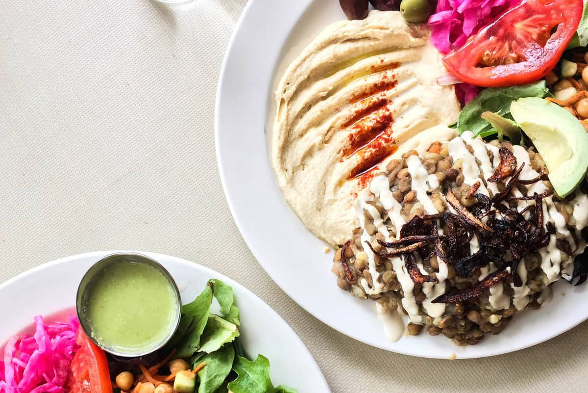 Overhead shot of two Mjadra plates with salad and hummus from Cafe Nuba in Vancouver.