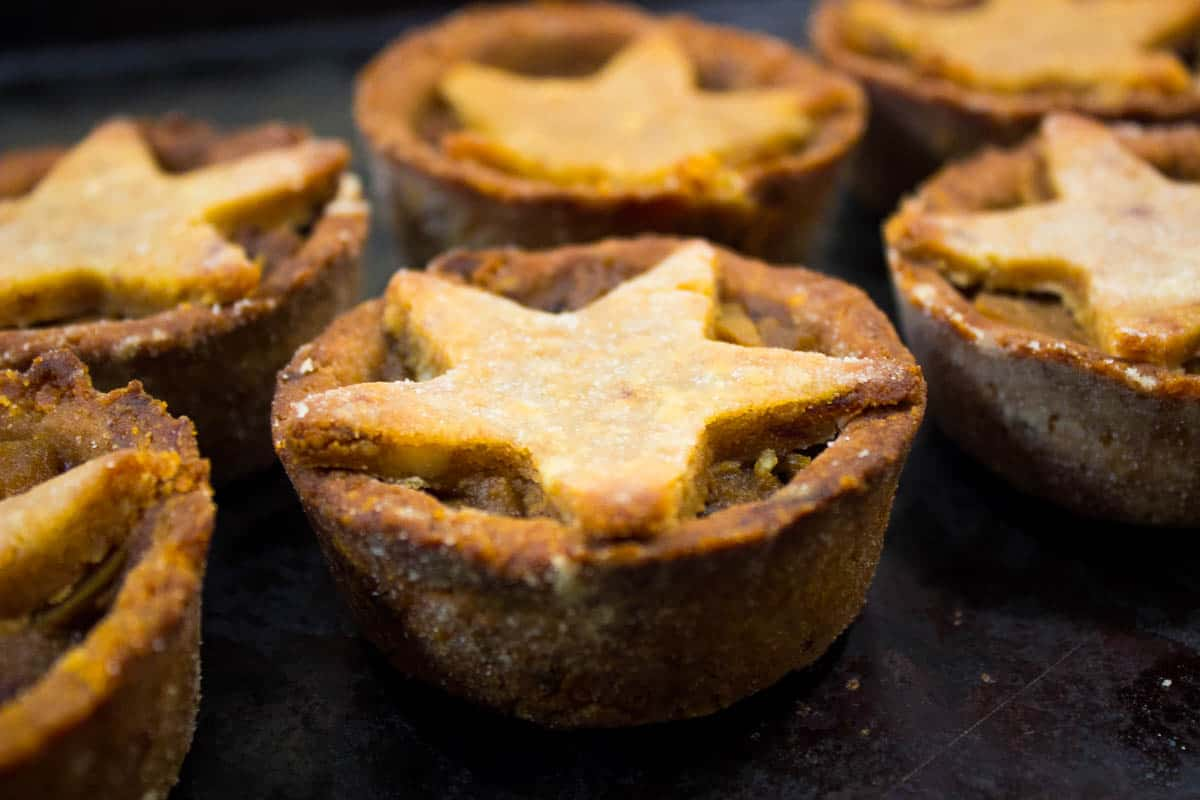 Festive Vegan Mince Pies (Vegan Christmas Recipes). Close up image shows several golden mince pies with pastry star tops on an old baking tray.