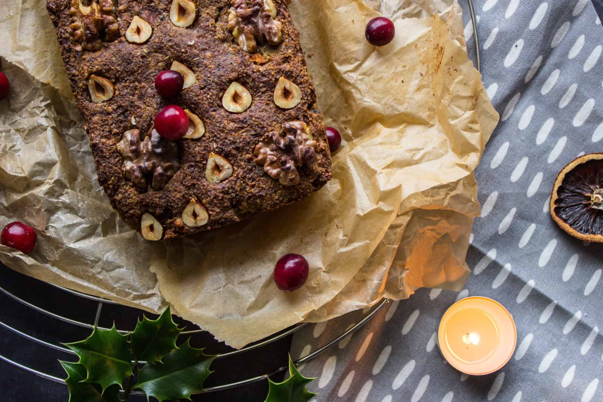 Vegan Christmas Recipes. Overhead closeup image of Classic Vegan Nut Roast (gluten-free). Picture shows a portions of a hazelnut-studded nut roast on baking parchment, surrounded by holly leaves, orange slices and cranberries. Some tealight candles and a grey patterned napkin are also visible.