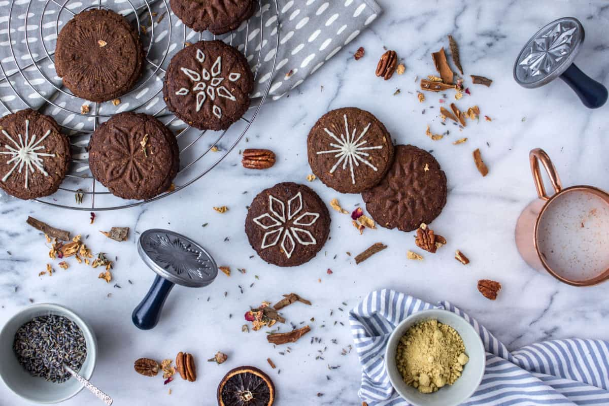 Wholesome Holiday Cookies (Vegan Christmas Recipes). Overhead image shows holiday cookies spread out on a white marble surface. Some are on a wire cooling rack and grey napkin. They are surrounded by pieces of cinnamon stick, orange slices, cookie cutters and spices.