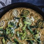 Close up overhead shot of Vegan Leek & Onion Frittata in cast iron skillet. Frittata is decorated with leek and onion discs.