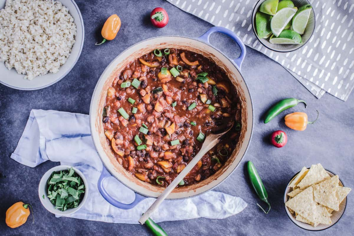 Overhead image of Homemade Vegan Chili in a large saucepan, surround by chilis, peppers, corn tortilla chips, a bowl of lime wedges and rice.