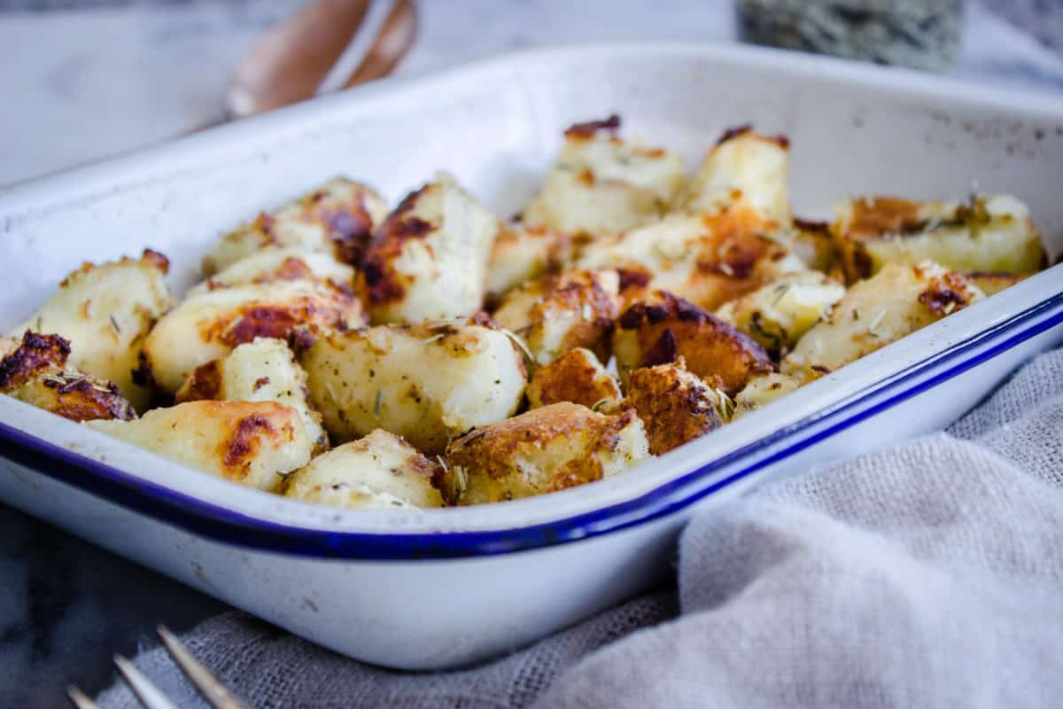 Crispy Rosemary Roast Potatoes. (Vegan Christmas Recipes) Image shows a white enamel tray of roast potatoes, surrounded by a beige linen napkin, jar of dried rosemary and silver serving fork.