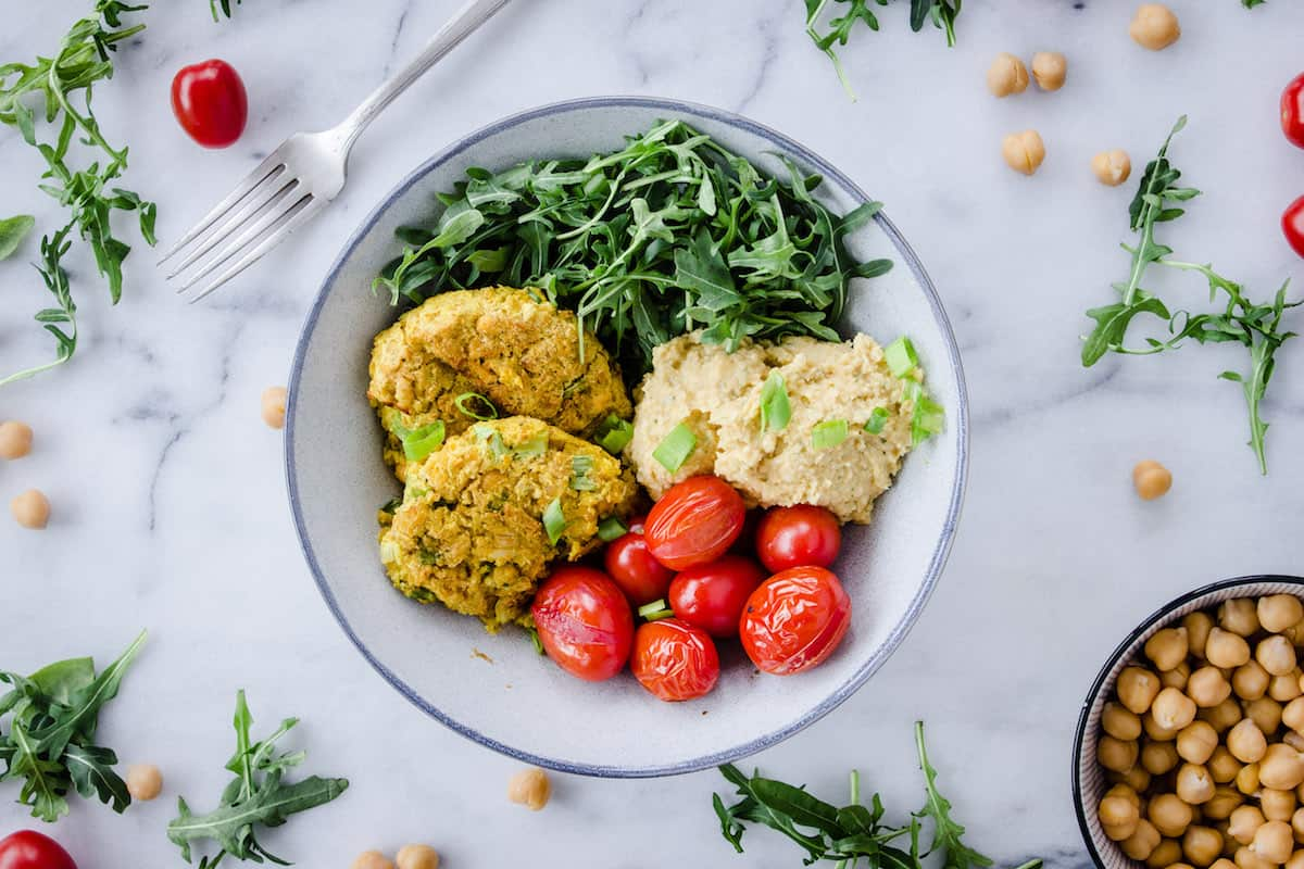 Overhead image shows Easy Vegan Chickpea Fritter Bowls on a white marble background. Bowl is filled with chickpea fritters, roasted cherry tomatoes, arugula and hummus. Tomatoes, chickpeas and arugula are scattered around the bowl.
