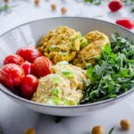 Image shows Easy Vegan Chickpea Fritter Bowls on a white marble background. Bowl is filled with chickpea fritters, roasted cherry tomatoes, arugula and hummus. Tomatoes, chickpeas and arugula are scattered around the bowl.