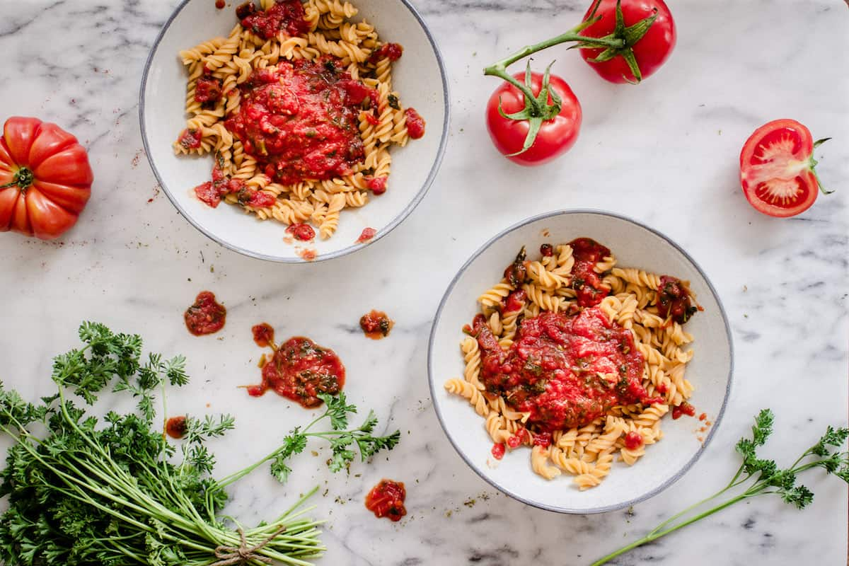Overhead view of two bowls of pasta with tomato sauce, surrounded by parsley and tomatoes.