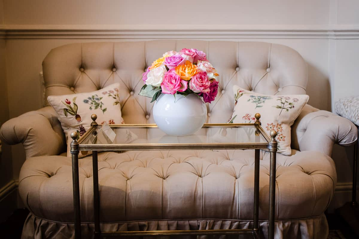 Image shows a sofa in the sitting room of Egerton House Hotel, with a vase of pink and yellow roses on it.