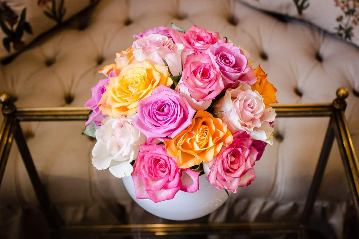 Image shows a vase of pink and yellow roses on a coffee table in the sitting room of Egerton House Hotel.