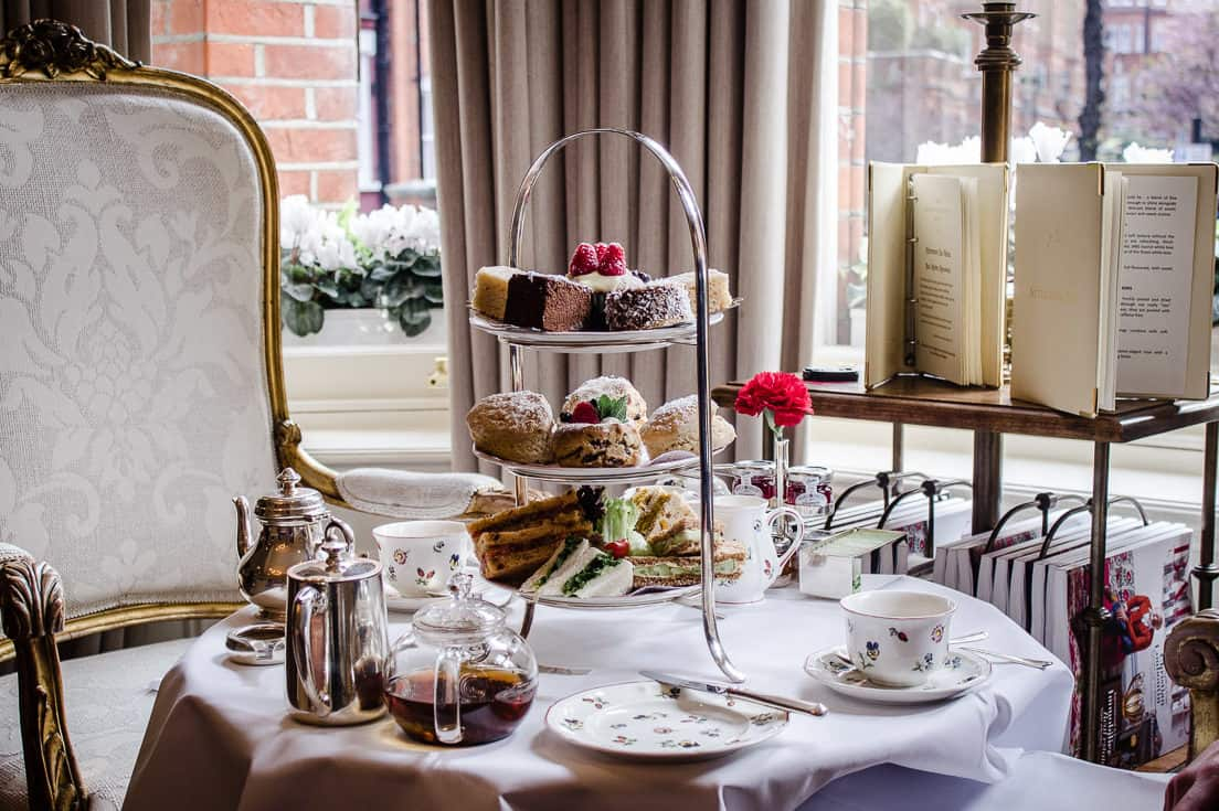 Image shows Egerton House's Vegan Afternoon Tea. There is a table set for two in a sitting room with a comfortable chair beside it. On the table is a three-tiered cake stand containing sandwiches, scones and cakes, surrounded by pots of tea and china cups/plates.