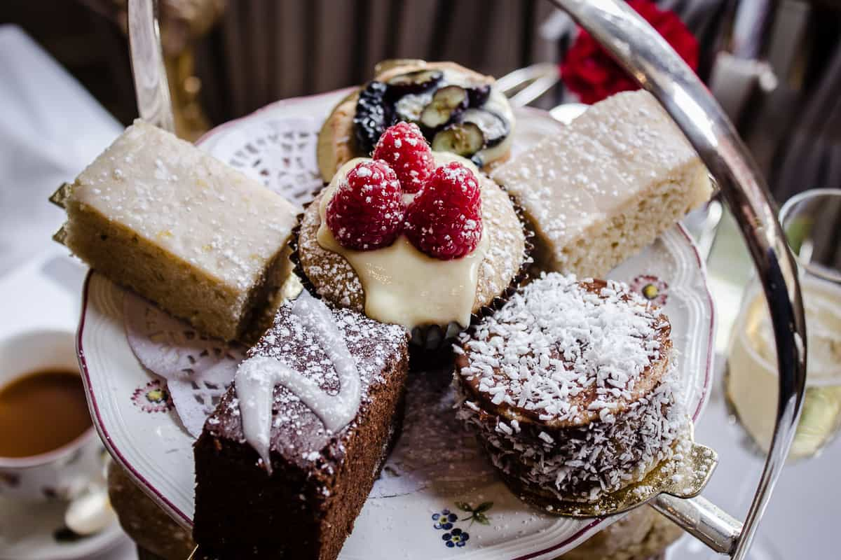 Image shows a close-up of the cakes from Egerton House's Vegan Afternoon Tea. The top tier of a cake stand is shown, featuring a raspberry-topped cupcake, two rectangular lemon cakes, a blueberry tart and a chocolate brownie.