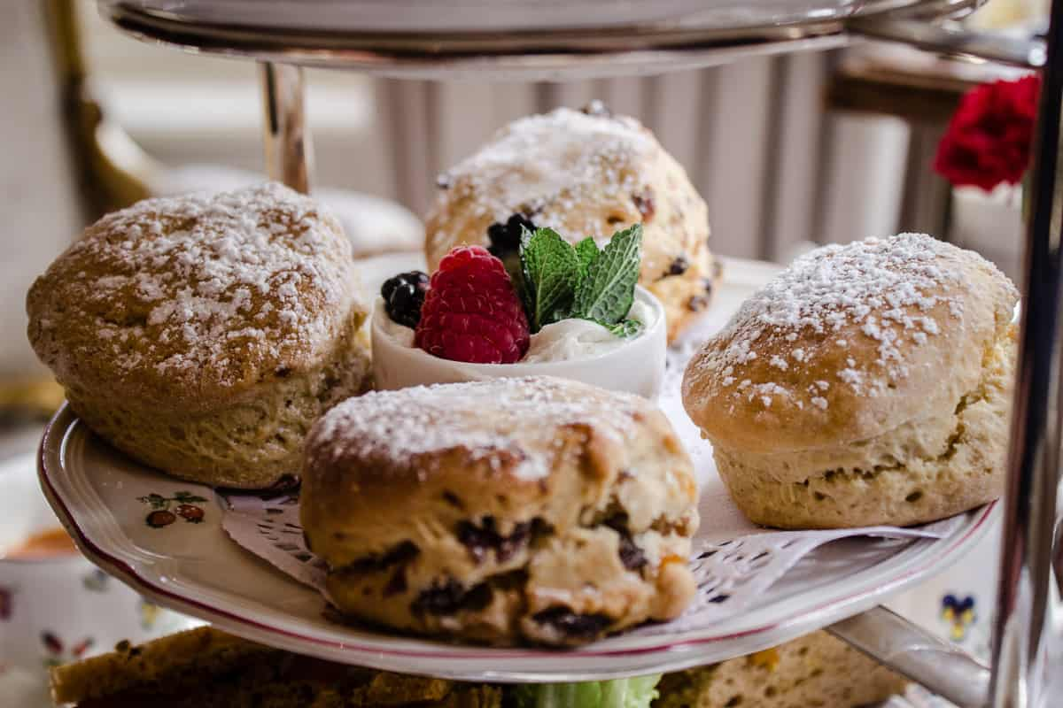 Image shows a close-up of the scones from Egerton House's Vegan Afternoon Tea. The middle tier of a cake stand is shown, featuring four scones surrounding a dish of coconut cream and berries.