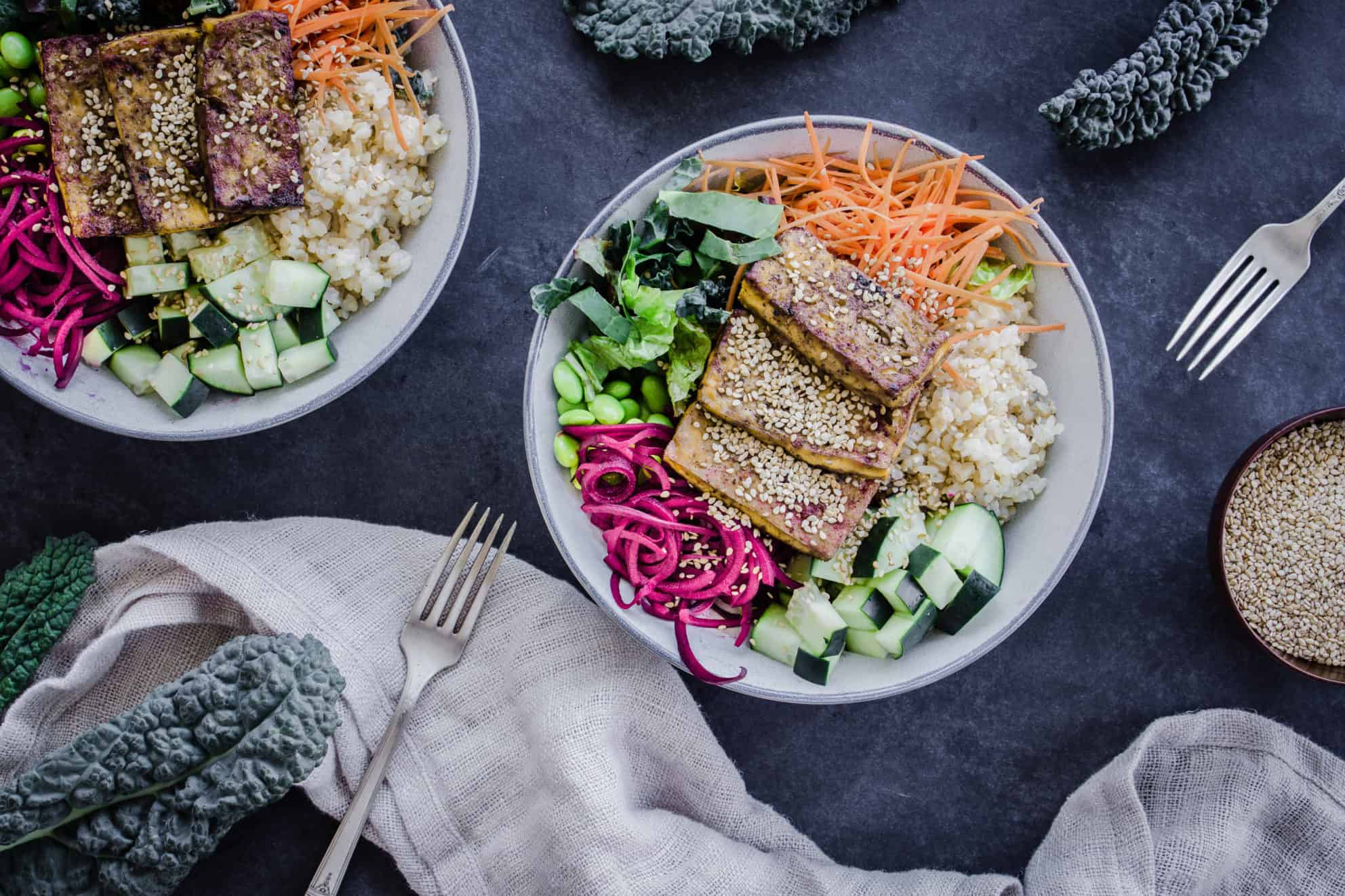 Two colourful vegan buddha bowls containing rice, vegetables and tofu, surrounded by forks, napkins, sesame seeds and kale leaves.