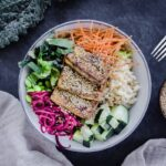 One colourful vegan buddha bowl containing rice, vegetables and tofu, surrounded a fork, napkin, sesame seeds and kale leaves.