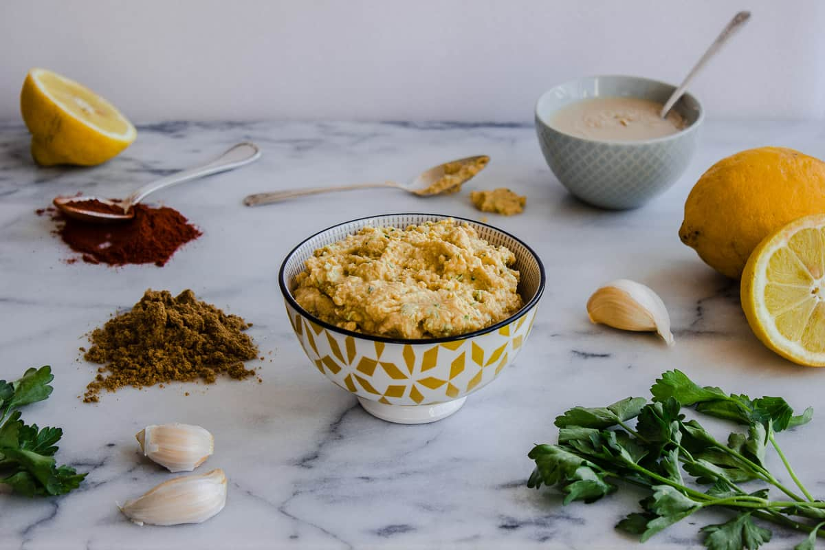 Image of hummus in bowl surrounded by ingredients such as lemons, tahini, coriander, garlic and parsley.