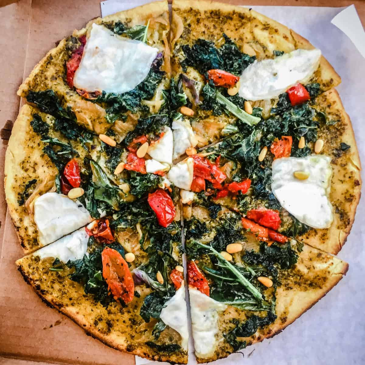 Overhead shot of pizza topped with vegan cheese, tomatoes, kale and pine nuts from Virtuous Pie Restaurant in Vancouver.