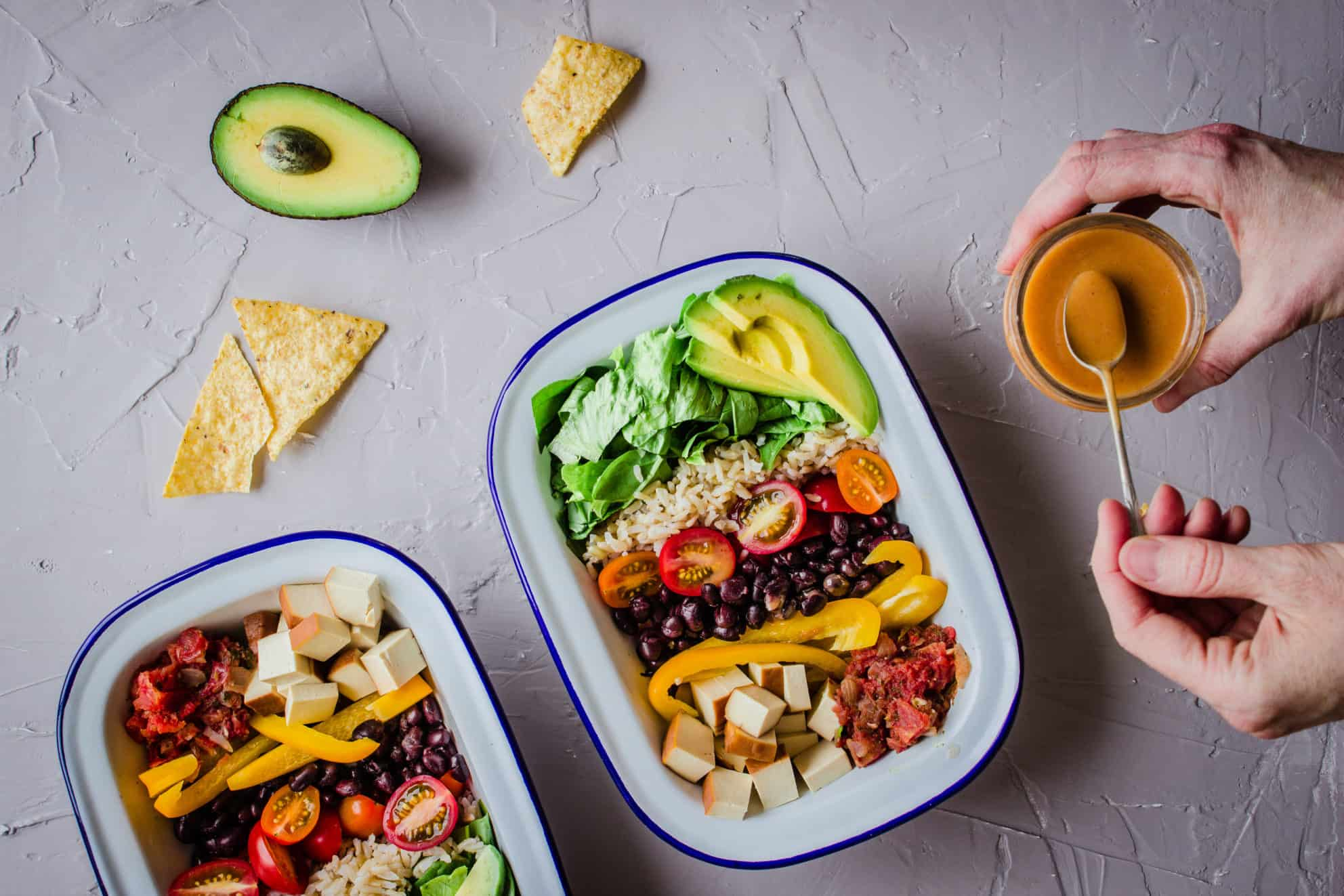 Overhead shot of Healthy Mexican Bowls with Salsa, surrounded by avocado, tortilla chips and woman's hands holding pot of dressing.