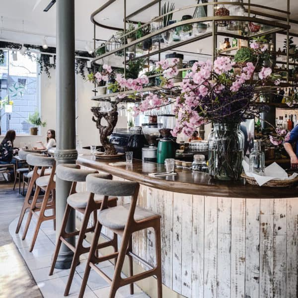 Image of My Favourite Vegan Restaurants in London - flower-covered bar with stools at Farmacy