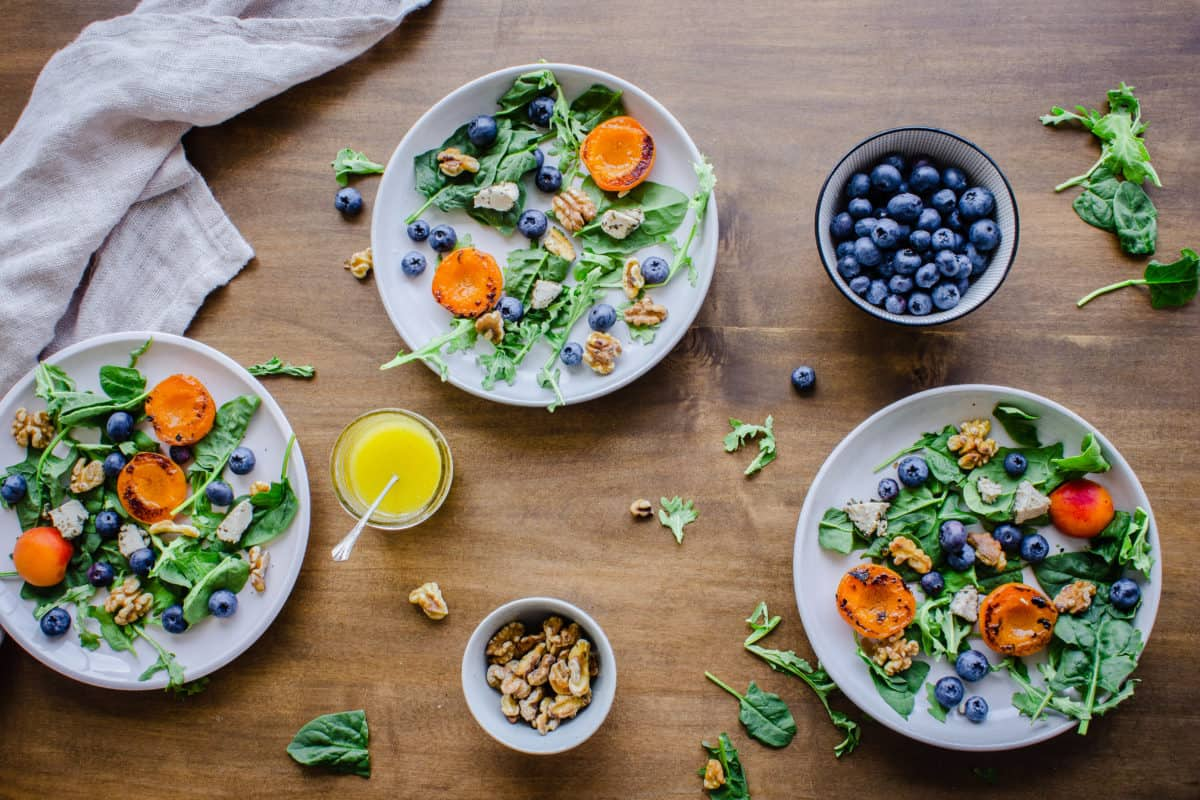 Overhead shot of Easy Apricot Blueberry Salad on wooden table, surrounded by linen napkin, bowl of blueberries, bowl of walnuts, lemon dressing and arugula.