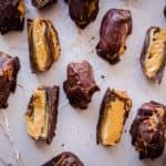Overhead shot of Chocolate Peanut Butter Stuffed Dates on light grey plaster background.