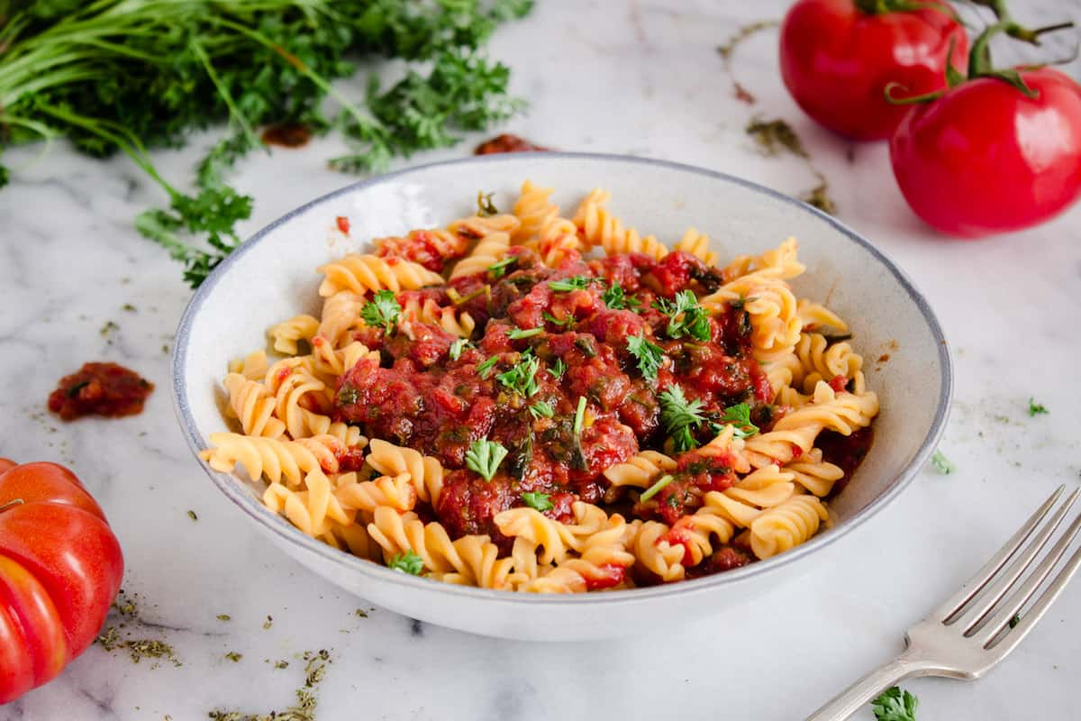 How to Go Vegan (10 Easy Steps). Image shows a plate of pasta with homemade tomato sauce.