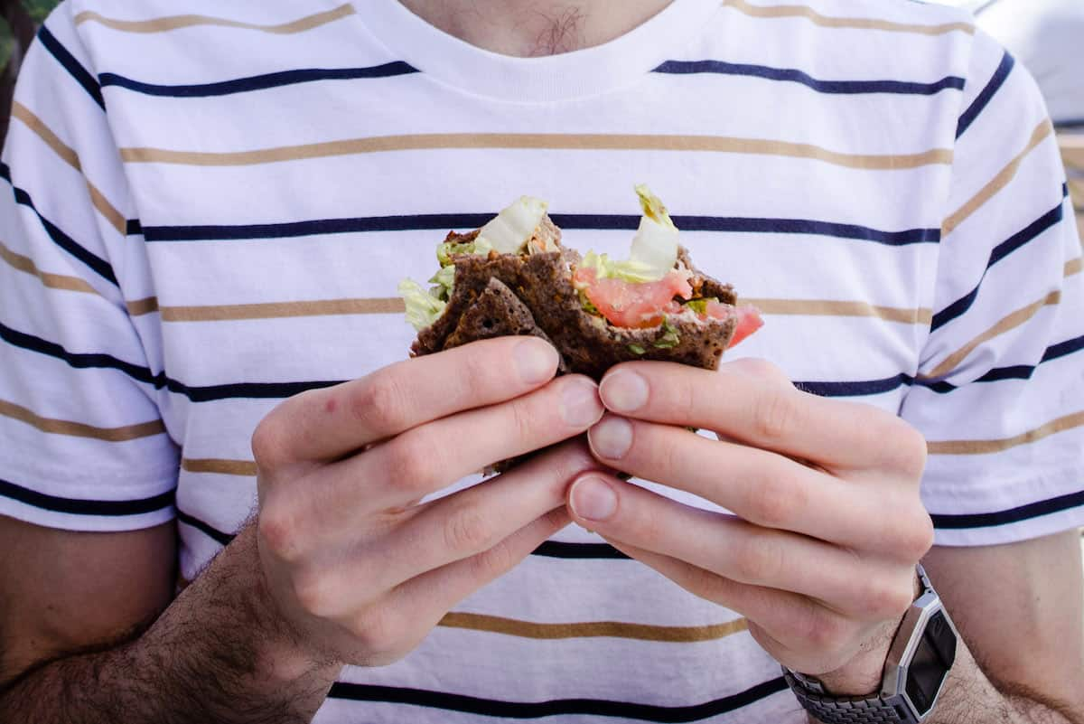 Man in a light-coloured stripy t-shirt holds a raw sandwich filled with lettuce, tomato and other vegetables.