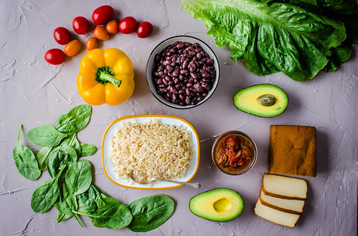 How to Go Vegan (10 Steps to Make it Stick) - Vancouver with Love. Overhead image of vegan ingredients, including colourful vegetables, brown rice, black beans, tofu and salsa.