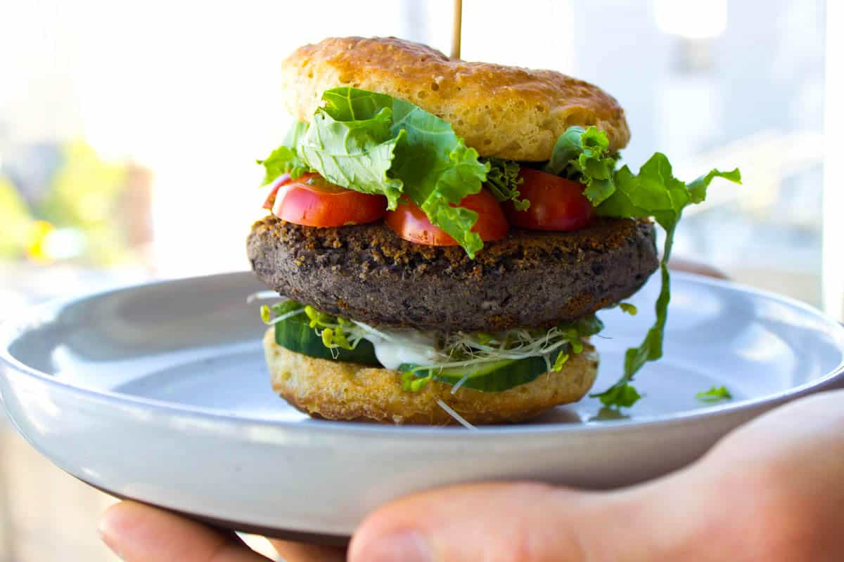 A vegan burger on a plate, filled with tomatoes, lettuce, cucumber and sprouts.