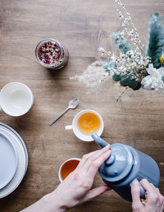 About & Contact - Vancouver with Love. Overhead shot of hands pouring tea from a teapot on a table, surrounds by flowers, plates and cups.