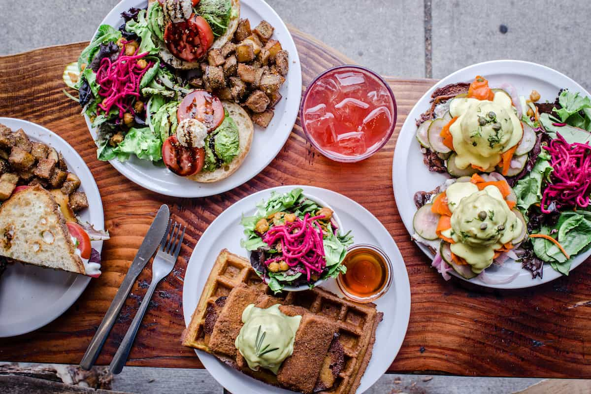 Overhead shot of four plates of vegan breakfast food photographed outside on Chickpea restaurant's terrace. The plates are full of colour and contain things such as vegan eggs benedict, waffles and hashbrowns.