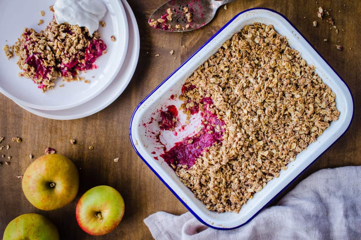 Overhead image of Apple & Blackberry Crumble. Image shows a white enamel tray of crumble with a pink apple and blackberry filling, and next to it a white plate with a serving of crumble and coconut yoghurt. The dishes are surrounded by an old silver cake slice, linen napkin, and apples, and are sitting on a wooden table.