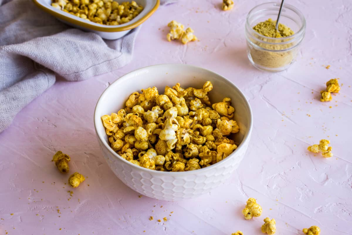 Image of two white bowls of Cheesy Vegan Popcorn on light pink plaster background, surrounded by scattered pieces of popcorn, a linen napkin and a glass jar of nutritional yeast.