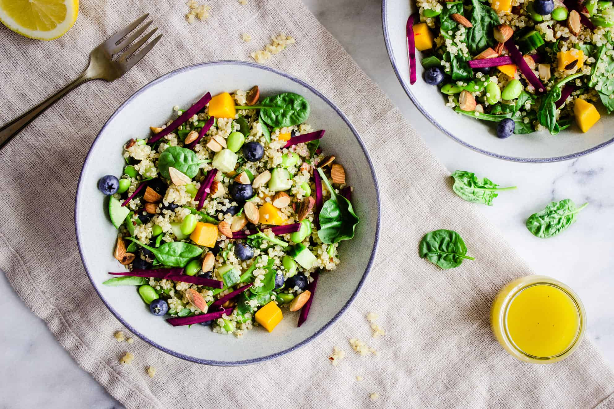 Overhead image of Quinoa Power Bowls, showing two grey bowls with quinoa, bright-coloured vegetables, fruit and toasted nuts in them, on a beige linen napkin accompanied by spinach leaves, quinoa, a lemon wedge and bright yellow vinaigrette.