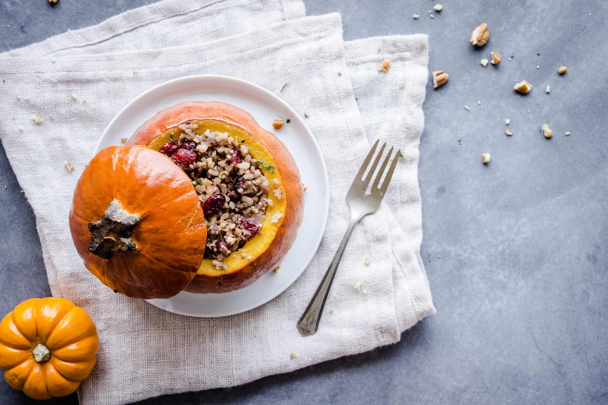 Overhead shot of Stuffed Pumpkin, showing a pumpkin with its lid off, stuffed with cranberries, rice and nuts on a white plate. The plate is on a folded linen napkin which is sitting on a grey table. To one side is a smaller pumpkin, silver cutlery and pecan crumbs.