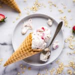 Overhead image of Vegan Strawberry Ice Cream with Cookie Dough. Image shows a waffle cone lying on a white plate, on a white marble surface with two scoops of ice cream in it. The cone is surrounded by an antique silver spoon and drips of ice cream. Also visible in the image is another cone, some strawberries and some oats.