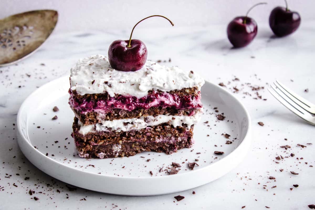 One slice of No-Bake Black Forest Cake sits on a white plate to the left of the image, surrounded by flakes of chocolate, some cherries and a silver fork. The cake is decorated with white coconut whipped cream and a single cherry.