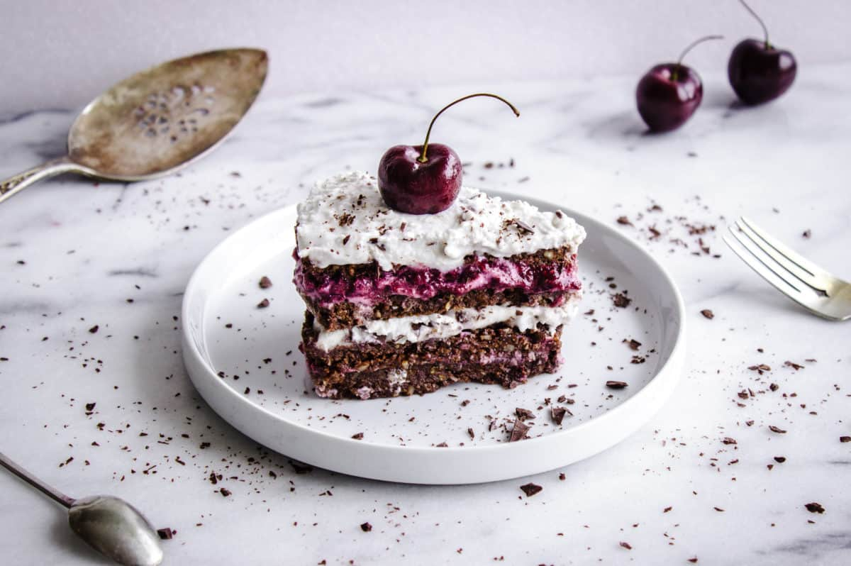 A single slice of cake is on a white plate on a white marble background, surrounded by cutlery and cherries. The slice is decorated with coconut whipped cream, a single cherry and dark chocolate flakes.