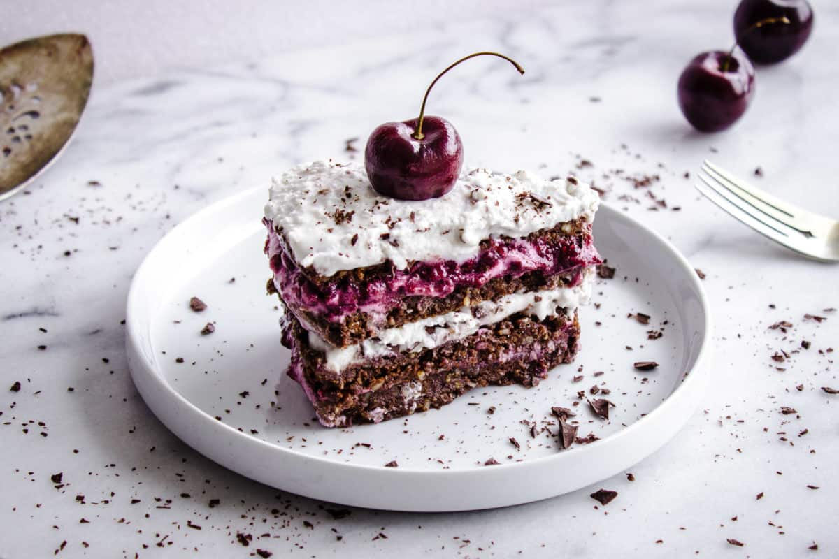 Shot of No-Bake Black Forest Cake, showing slice of chocolate-flavoured raw cake with layers of cherry jam and coconut cream. The cake is decorated with a whole cherry and chocolate shavings. It is placed on a white plate on a white marble countertop, and is surrounded by silver cutlery, a cake slice, cherries and more chocolate shavings.