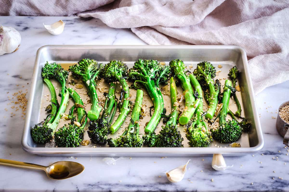 Image of Roasted Broccoli with Sesame & Garlic. A silver baking tray of roasted broccoli is visible on a white marble background. Surrounding it is a golden spoon, a cup of sesame seeds, some garlic cloves and a linen napkin.