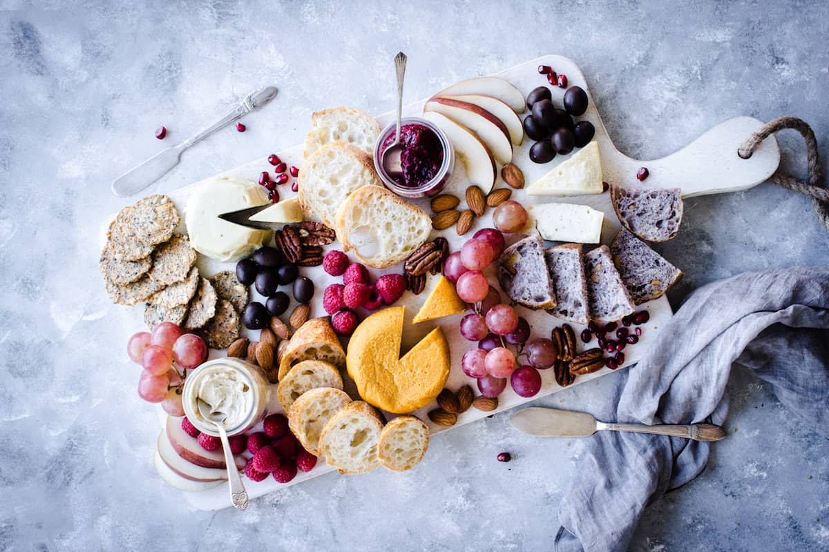 How to Make the Ultimate Vegan Cheese Board - Vancouver with Love. Image shows overhead view of a white vegan cheeseboard. The cheeseboard contains a mixture of orange and white wheels and wedges of cheese, a mix of breads and crackers, jars of preserves and spreads, fruits and berries and a mixture of nuts. It consists of mainly pink, yellow, orange and neutral tones. Several antique silver cheese knives and spoons are placed on and around the board. It is on a mottled grey background and there is a grey napkin in shot.