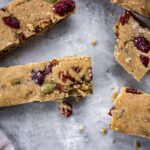 Image of vegan granola bars with cranberries, nuts and pumpkin seeds on a grey mottled background.