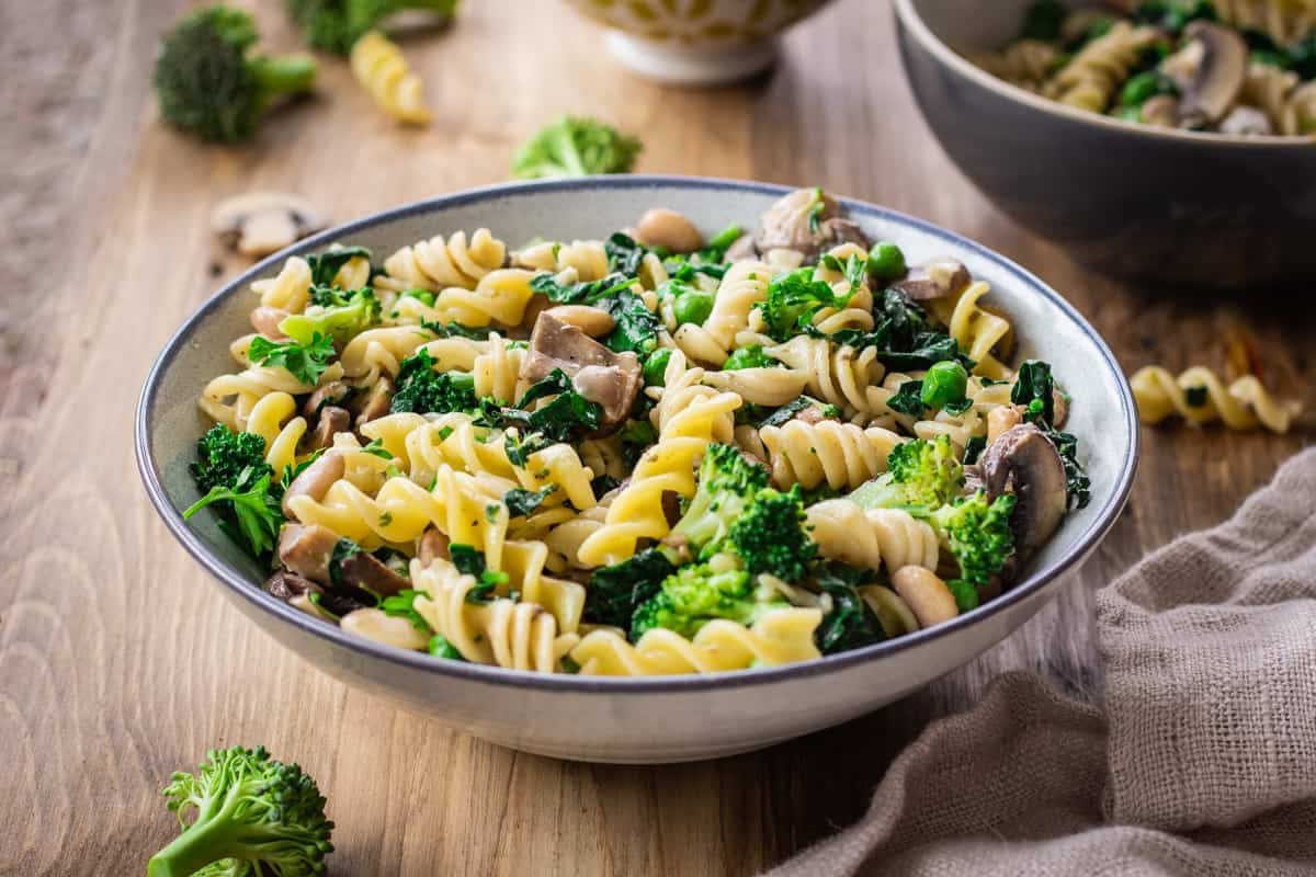 Image shows bowl of Creamy Pasta with Broccoli & Mushrooms on a wooden table. The bowl is surrounded by a linen napkin, bits of pasta and other bowls.