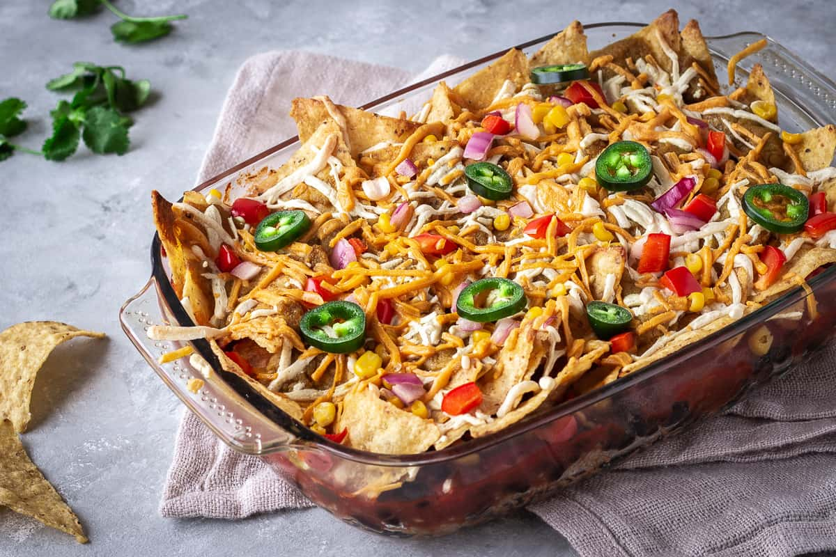 Image shows Hearty Nacho Bake decorated with vegan cheese shreds and jalapenos. The bake is surrounded by cilantro and scattered Que Pasa Salted Tortilla Chips, and is made with their Mexicana Mild Salsa.