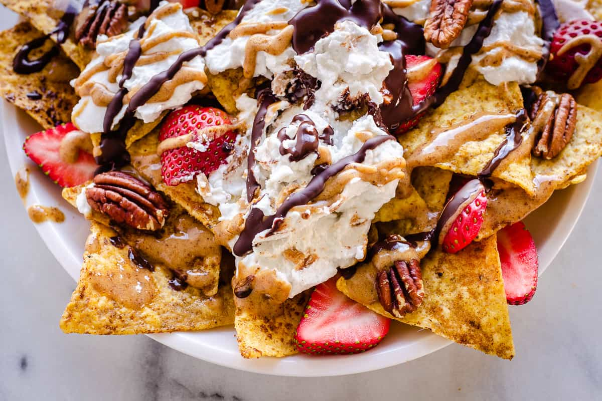 Close-up overhead image of Dessert Nachos . The nachos are decorated with strawberries, coconut whipped cream, pecans, drizzled chocolate and almond caramel sauce.