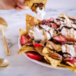 Image of Dessert Nachos showing a hand taking a nacho with cream and chocolate on. The nachos are decorated with strawberries, coconut whipped cream, pecans, drizzled chocolate and almond caramel sauce.