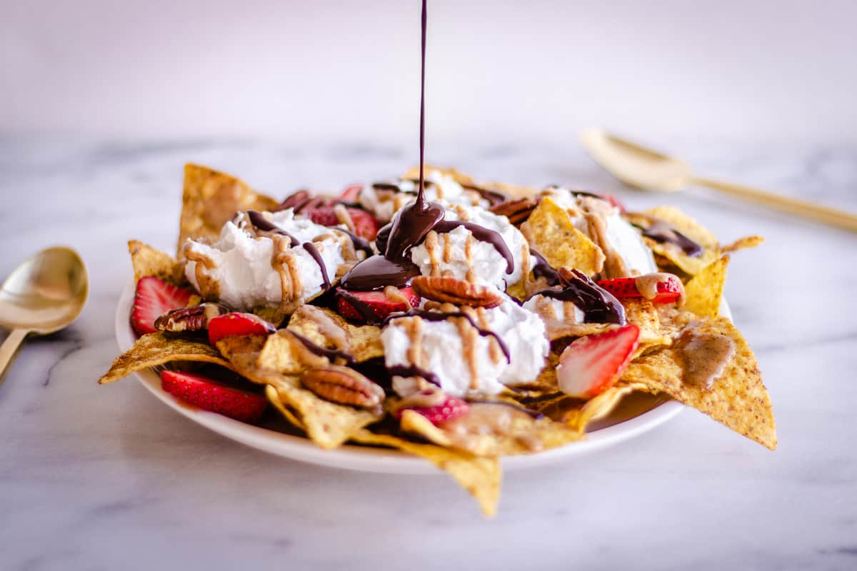 Image of Dessert Nachos showing dark chocolate being drizzled over them. The nachos are decorated with strawberries, coconut whipped cream, pecans, and almond caramel sauce.