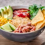 Close up image of Savoury Vegan Oatmeal in large bowl on wooden table. Oatmeal is topped with avocado, corn, salsa, tortilla chips, lime, cilantro and beans and a linen napkin is behind it.