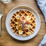 Overhead image of 3 Ingredient Oatmeal Waffle on a wooden table with a silver fork and blue & white striped napkin nearby. The waffle is decorated with bananas, almond butter, pecans and cacao nibs.