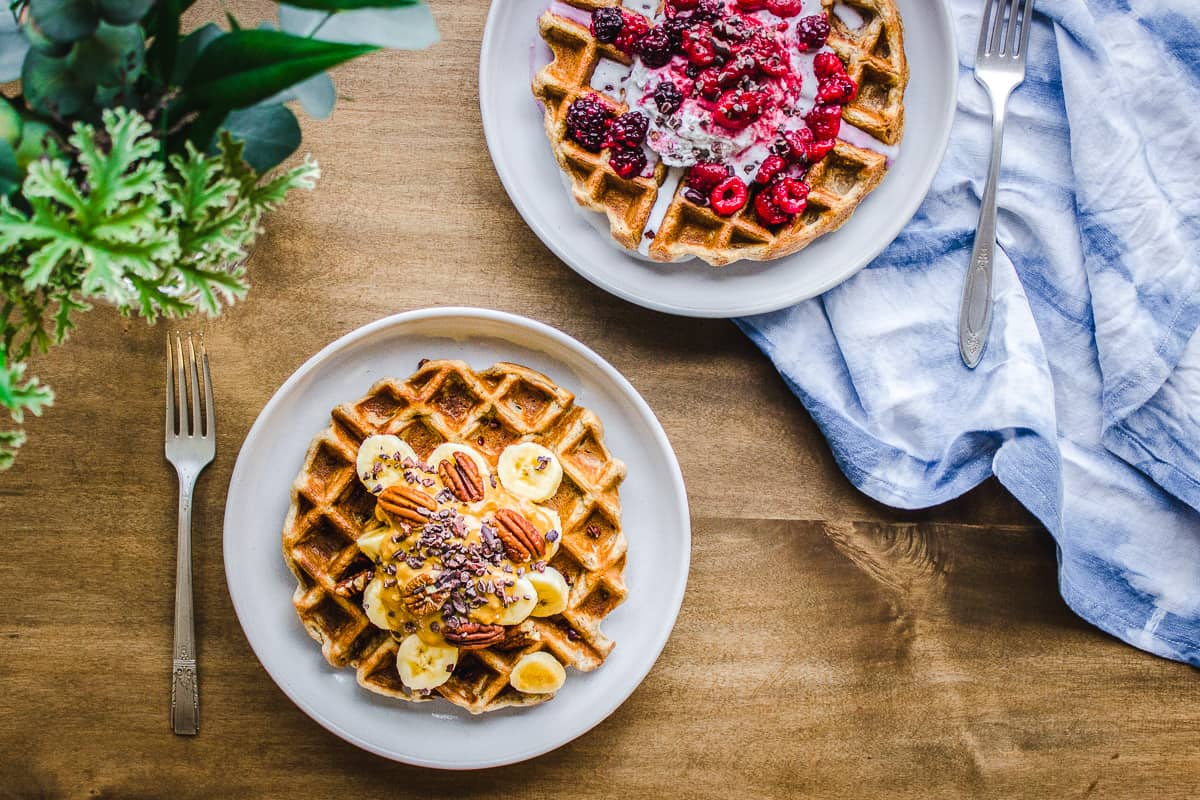Overhead image shows 3 Ingredient Oatmeal Waffles on a wooden table with a vase of green leaves and a blue and white napkin nearby. There are two plated waffles: the one below is decorated with bananas, almond butter, pecans and cacao nibs, and the one behind is decorated with berries and whipped coconut cream.